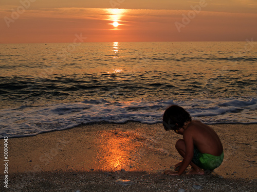 Little boy playing on the beach at sunset