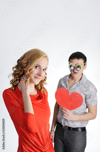 Beautiful blond and shocked young man in glasses with valentine