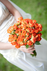The bride have orange wedding bouquet