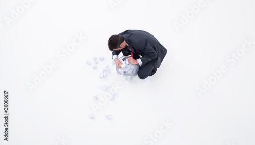 Businessman searching wastebasket with crumpled paper