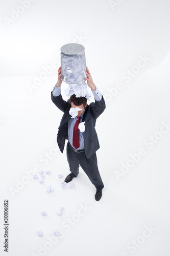 Businessman spilling out wastebasket with crumpled paper