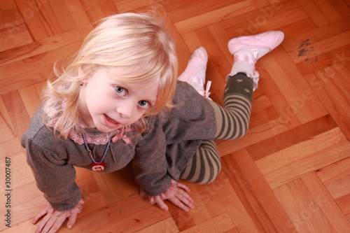 cute little blonde girl on the parquet