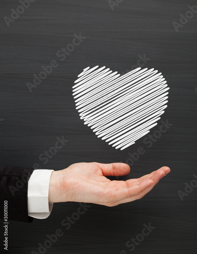 hand holding heart drawn on the blackboard