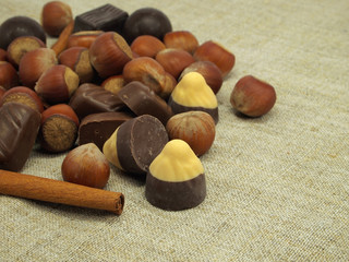 Cinnamon sticks, chocolate candies and hazelnuts