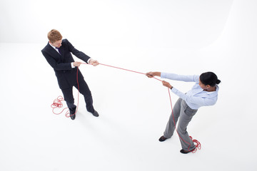 Businessman and businesswoman having tug-of-war with thread