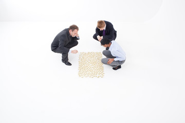 Businessmen and businesswoman looking at post-its on the floor