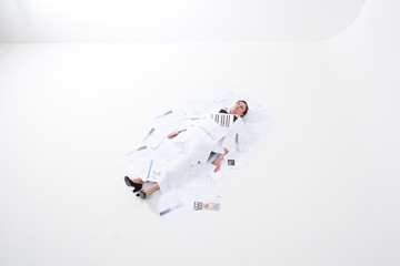 Businesswoman lying on floor covered with papers