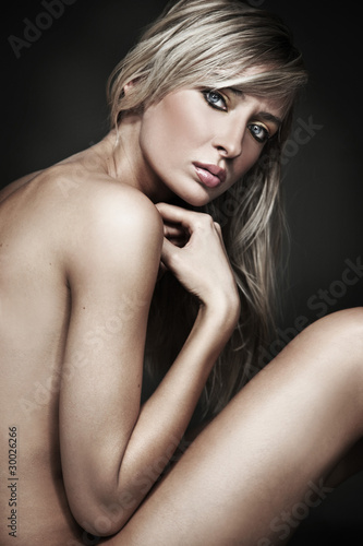 Beautiful sexy tanned naked young slim blond girl sitting