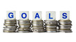 Stacks of coins with the word GOALS isolated on white