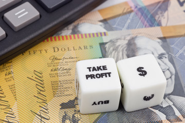 Australian currency with calculator and dice showing TAKE PROFIT