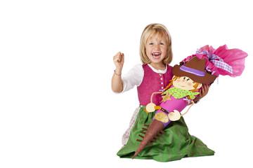 Mädchen mit Schultüte sitzt glücklich am Boden