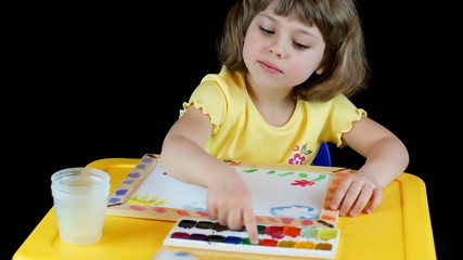 Little girl playing with watyercolors