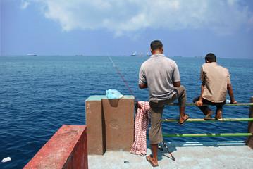 pescatori sulla diga di male
