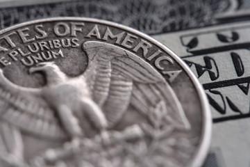 quarter dollar coin on the one hundred Dollar bill