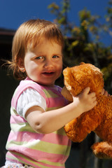 Young girl child outdoor play with her teddy bear