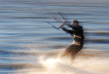 Kitesurfer goes fast int the water at the colors of sundown