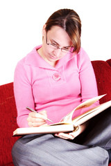 Casual young woman writing in a book