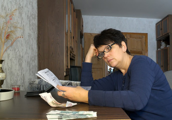 Thoughtful woman at a table with documents and money