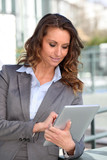 Smiling businesswoman using electronic tablet outside