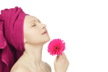 Young woman with towel and gerbera flower