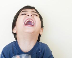 bambino che ride sporco di latte