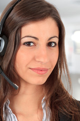 Smiling call center girl with office background