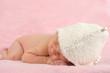 Neugeborenes liegt auf rosa Decke und schläft
