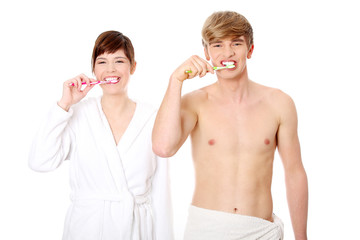 Young couple cleaning teeth together.