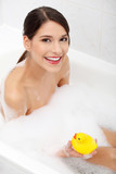 Woman taking a bath with yellow duck.