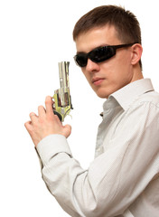 A guy with a gun in his hand wearing sunglasses on a white backg