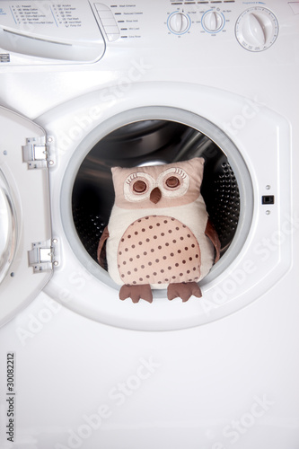 open washing machine with cuddly toy coming out or going in