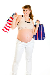 Happy pregnant female holding shopping bags in hands
