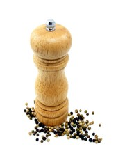 A wooden peppermill with peppercorns on white background