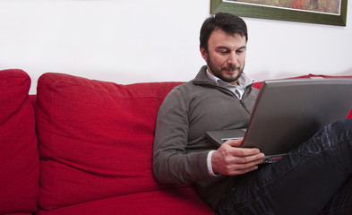 Portrait of a Relaxed Young Adult Using Laptop at Home