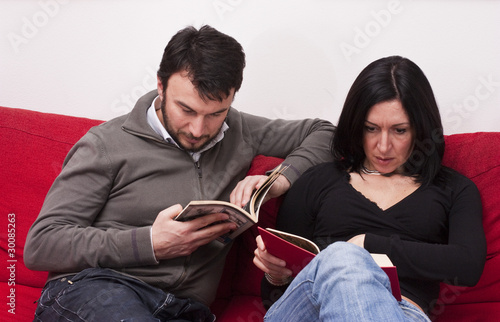 Portrait of Adult Couple Relaxing and Reading a Book at Home