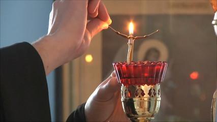 священник зажигает свечи