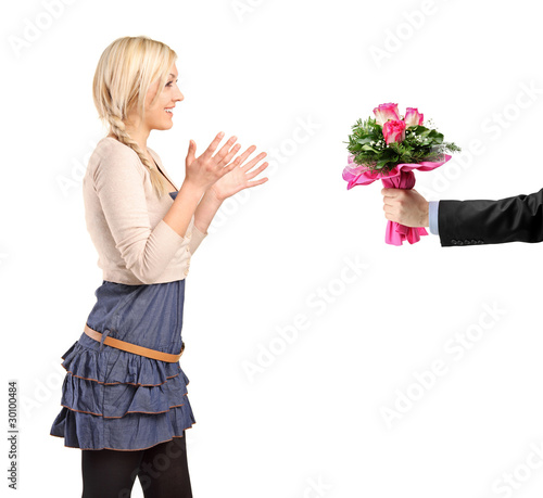 Surprised blond girl accepting bunch of flowers