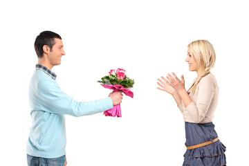 Boyfriend giving flowers to his surprised girlfriend