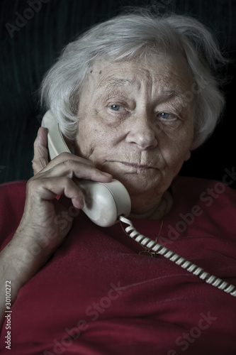 Pensive senior woman talking on the phone