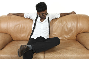 uomo affascinante seduto solo su un divano in pelle