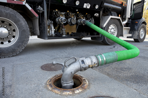 Fuel delivery tanker truck filling up storage tank