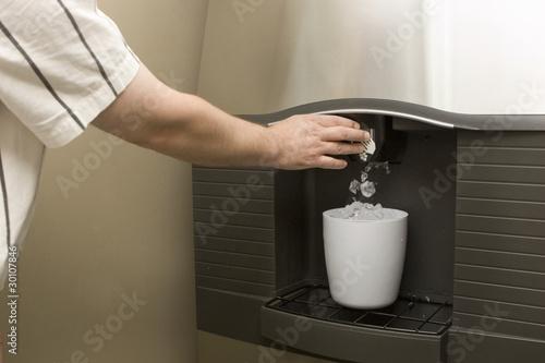 Leinwanddruck Bild Man filling bucket from Ice machine