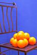 Orange auf einem Metallstuhl vor blauer Wand