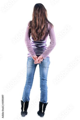 Beautiful young woman looking at wall. Rear view.