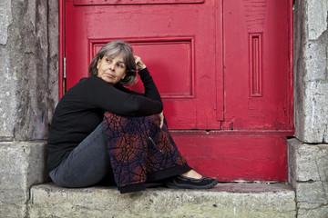 Woman sitting on door stoop