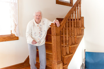 Senior woman standing in front of  stairs
