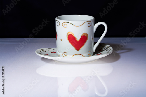 White cup with hearts stands on a white table.