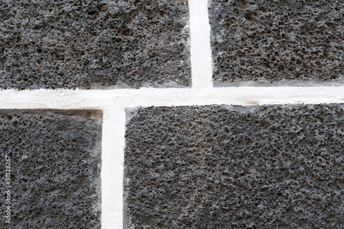Dark volcanic bricks with white cement joints, pattern