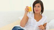 Cute brunette woman drinking a glass of orange juice