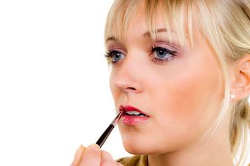 junge frau beim auftragen von lippgloss